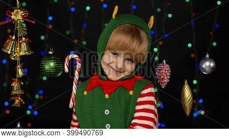 Shy Shamed Child Girl In Christmas Elf Santa Helper Costume Posing And Smiling. Kid Feels Guilty. Is