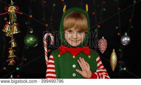 Teen Kid Girl 5-6 Years Old In Christmas Elf Santa Helper Costume Waving Greeting With Hand As Notic