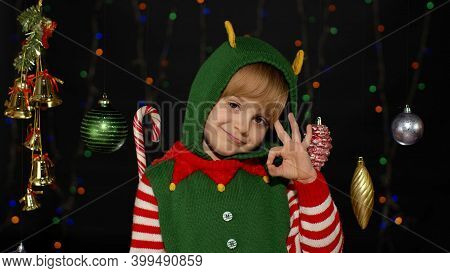 Blonde Teen Kid Girl In Christmas Elf Santa Claus Helper Costume Showing Okay Sign Isolated On Black
