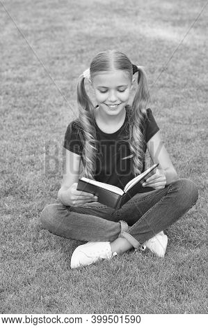 For Reading Addicts. Happy Child Read Book On Green Grass. Little Girl Enjoy Reading Summer Outdoors