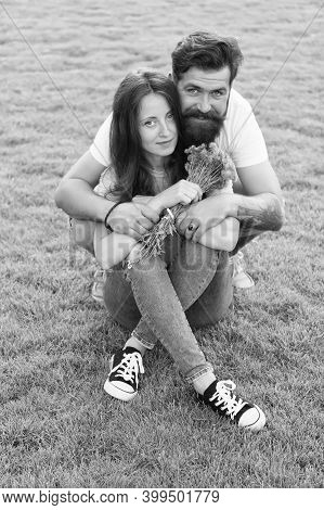Happy Womens Day. Bearded Man Give Flowers To Sexy Woman. Happy Couple In Love On Green Grass. Celeb