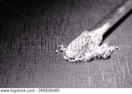 Spatula With Small Portion Of Calcium Carbonate, Isolated Black Background