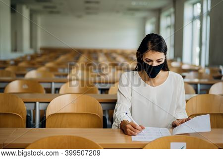 Female Student Taking An Exam Wearing A Protective Face Mask In An Empty Amphitheater. Stressed Stud
