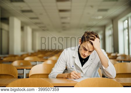 Medical Professional Filling Out A Document, Looking Exhausted, Tired. Doctor Writing An Opinion.med