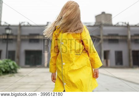 Little Caucasian Girl 7 Years Old With Blonde Hair In Yellow Raincoat. Colors Of The Year 2021 Ultim