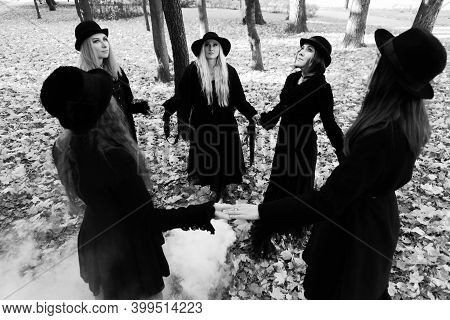 Coven Of Witches, Modern Witches Gathered And Do A Ritual In The Park. Halloween, A Group Of Differe
