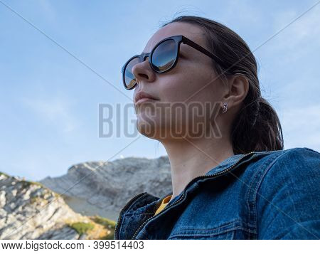 Young Female Tourist Enjoys Beautiful Nature. Reflection Of Mountains In Sunglasses, Beautiful Natur