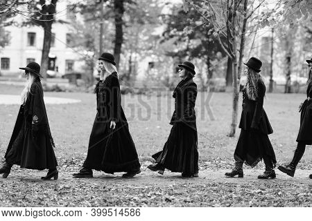 Five Women As Witches Go To The Sabbath, A Group Of Witches Or Goths In Black Clothes And Hats Go Do