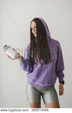Young And Active European Woman In Sports Outfit Holding A Plastic Water Bottle Or Protein Shaker. P