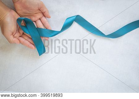 Hands Holding Teal Color Ribbon On White Fabric With Copy Space. Ovarian Cancer Awareness, Gynecolog