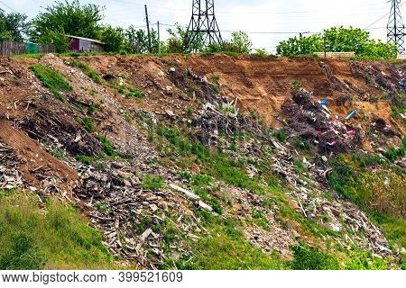 A Steep Hillside Sloping Down To The River Littered With Trash Thrown By Locals In The Village. Slop