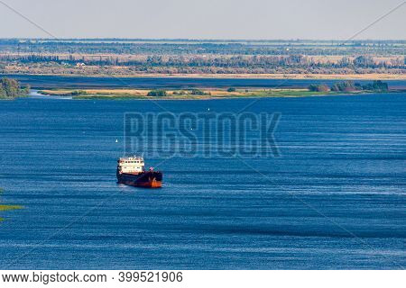 Large Dry Cargo Ship With A Black Hull Anchored Along The Big River.