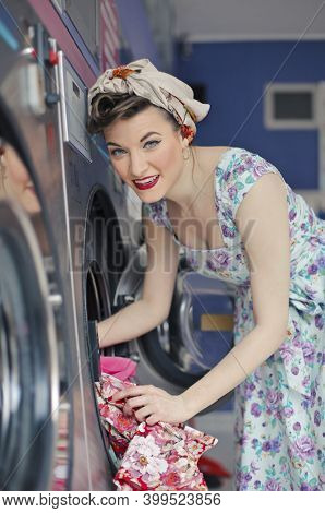young woman puts the laundry in a public washing machine