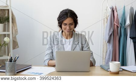 Happy Young Businesswoman Self-employed Tailor Sitting At Desk Using Laptop