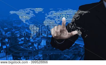 Businessman Pressing 2021 Start Up Business Icon With Global Words World Map Over Modern City Tower,