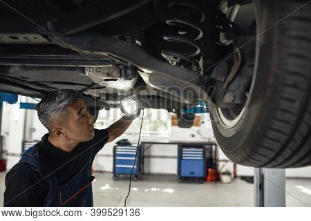 Young Asian Mechanic With Flashlight Looking For Damages On Auto Bottom Raised On Lift At Car Servic