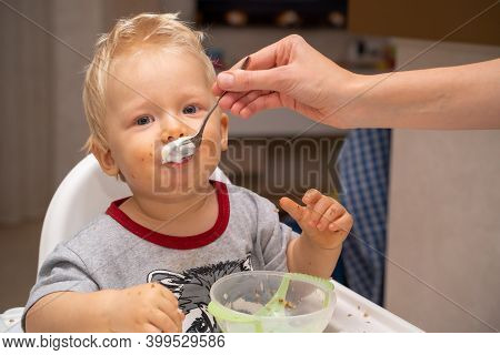 Mom Feeds The Blond Baby With Porridge From A Spoon. Little Boy Smeared His Face With Buckwheat Porr