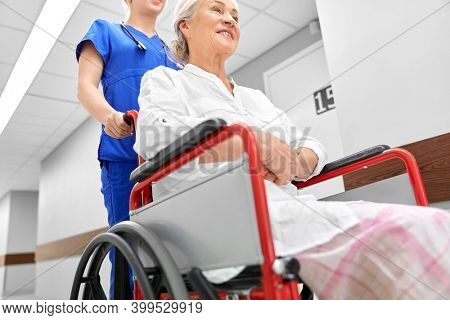 medicine, health and care concept - nurse taking happy smiling senior woman patient in wheelchair at hospital corridor or nursing home