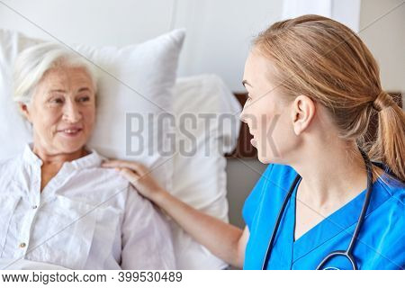 medicine, age, support, health care and people concept - close up of doctor or nurse visiting and cheering senior woman lying in bed at hospital ward