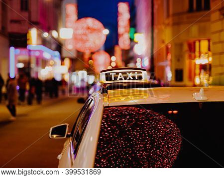 Taxi Car During Night In The City Of Vienna, Austria. Illuminated Neon Lights In The Streets Of The