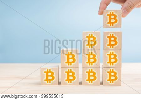 Hand Arranging Wood Block Cubes With Bitcoin Icon. Orange Bitcoin Signs On Wooden Blocks Lined With