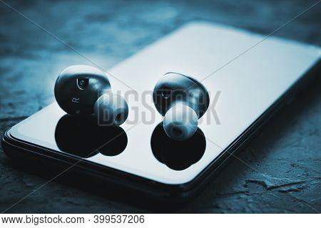 Wireless Earphones On A Smartphone, Toned Photo. Bluetooth Headphones For Listen Audio