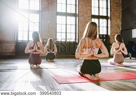 Group Of Young Women Do Complex Of Stretching Yoga Asanas In Loft Style Class.