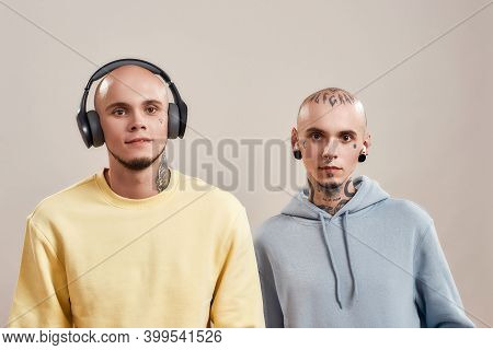 Two Young Caucasian Twin Brothers In Casual Wear With Tattoos And Piercings Listening Music In Headp