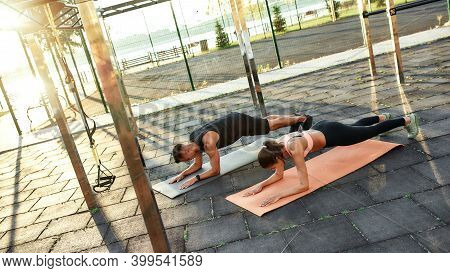 Top View Of Sportive Man And Woman Performing Elbow Plank Exercise On Street Playground In Summer, O