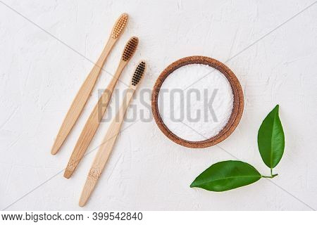 Three Wooden Bamboo Toothbrushes And Baking Soda On A White Background, Top View. Eco Friendly Tooth