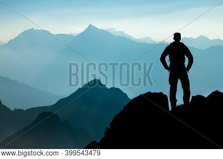 One Man Reaching Summit After Climbing And Hiking Enjoying Freedom And Looking Towards Mountains Sil