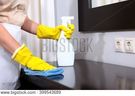 Cleaning In The Hotel Or In The House. A Maid In Protective Gloves Wipes The Furniture In A Hotel Ro