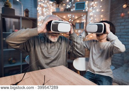 Grandfather And Grandson Are Using Virtual Reality At Night At Home.