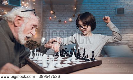 Grandfather And Grandson Are Playing Chess Together At Night At Home. Boy Is Winning.