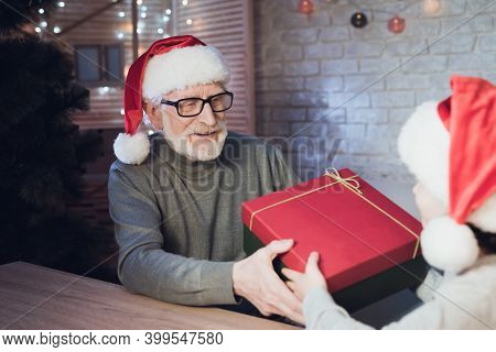 Grandfather And Grandson In Santa Claus's Hats At Night At Home. Granddad Is Giving Boy Present.