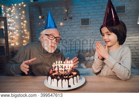 Grandfather And Grandson At Night At Home. Birthday Party. Granddad Is Blowing Birthday Cake Candles