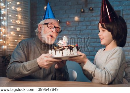 Grandfather And Grandson At Night At Home. Birthday Party. Granddad Is Giving Boy Birthday Cake.