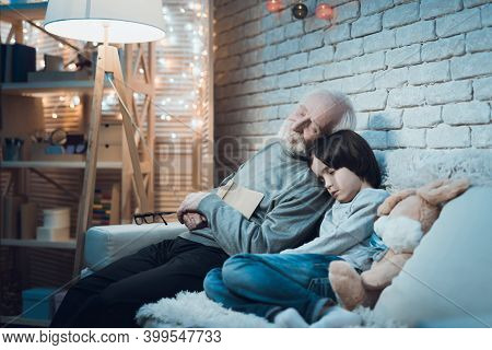 Grandson And Grandfather Wave In Laptop While Chatting. Grandfather And Grandson Talking With Someon