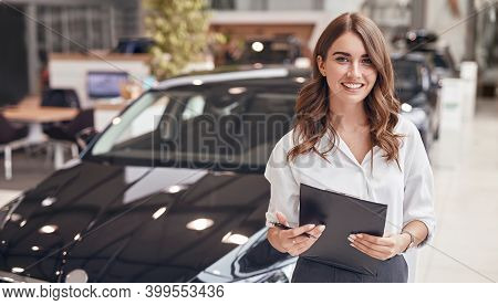Smiling Elegant Woman With Clipboard Working In Car Showroom Smiling Friendly At Camera