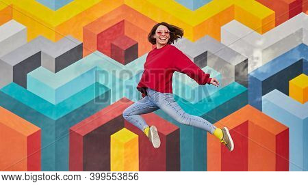 Full Body Delighted Female Hipster In Stylish Outfit Leaping Against Wall With Colorful Geometric Or