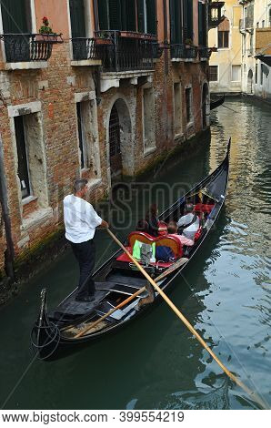 Venice, Italy - Sept 25, 2014: Venice Canal And Gondola With Tourists. Tourists From All The World E