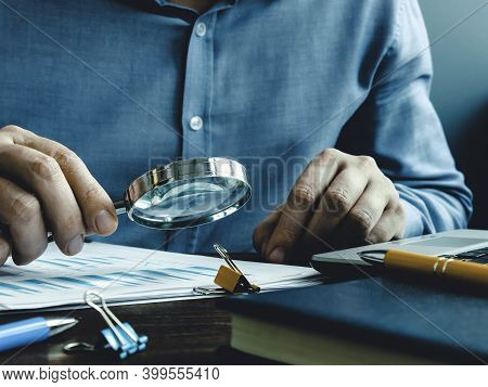 The Auditor Checks The Accounting Records And Reports With Magnifying Glass.