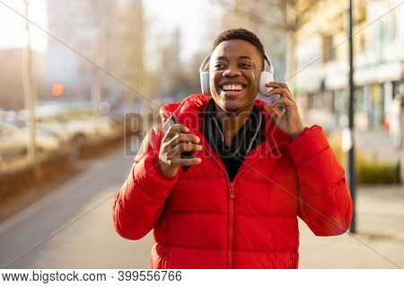 Young man wearing headphones and listening to music in the city