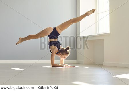 Young Female Gymnast Doing Arm Stand While Practicing Gymnastics In Modern Sunny Studio
