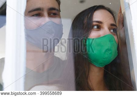Caucasian couple wearing face masks looking out of window smiling. self isolation at home during covid 19 coronavirus pandemic.
