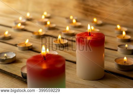 Candles On A Wooden Background. A Red Sick Candle That Changes Color When You Light It And Small Can
