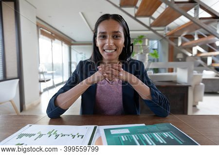 Smiling mixed race woman wearing phone headset during video call at home. self isolation during covid 19 coronavirus pandemic.