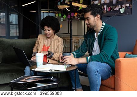 Diverse businessman and businesswoman using laptop having coffee on their break in office. technology and social distancing in business office workplace during covid 19 coronavirus pandemic.