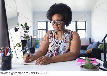 African american female vlogger recording a video writing in notebook. self isolation technology communication at home during coronavirus covid 19 pandemic.