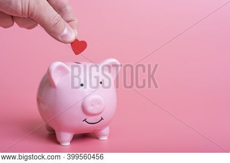 Close-up Of A Manual Deposit Red Heart In A Piggy Bank On A Pink Background